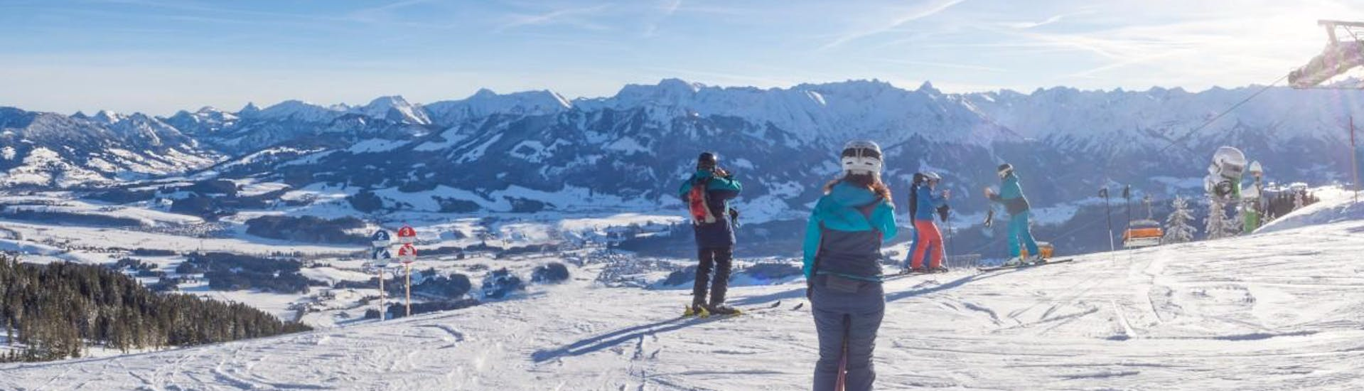 A group of people are at the top of the mountain looking out over the Bavarian ski resort of Bolsterlang, where local ski schools offer a ski lessons to visitors who want to learn to ski.
