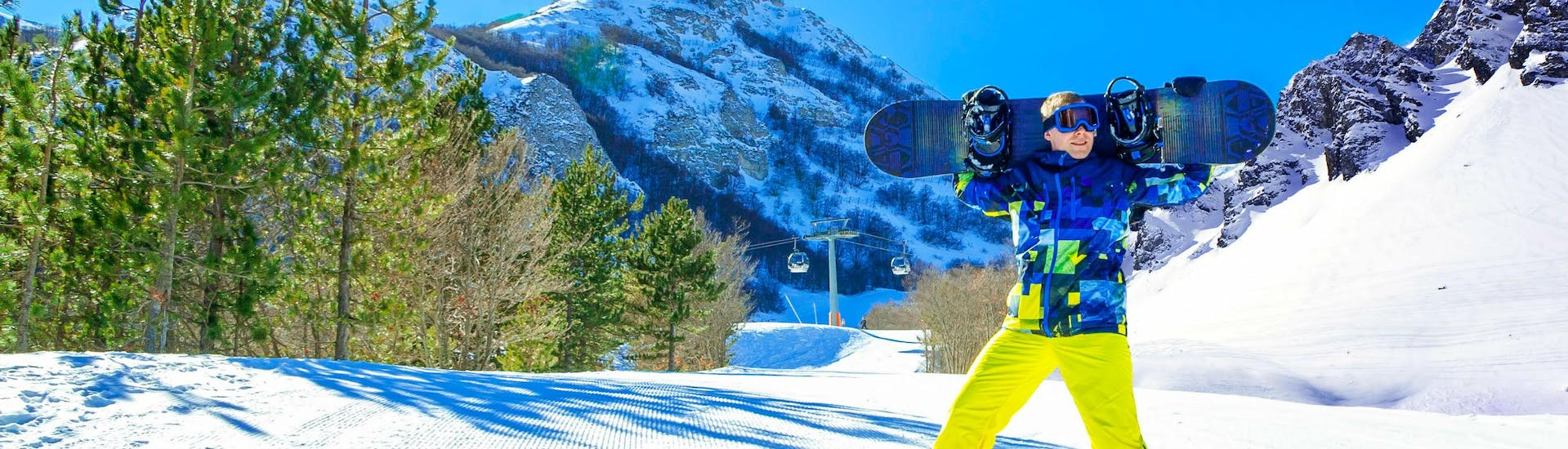 A snowboarder is posing for the camera on a sunny ski slope in the Italian ski resort of Campo Felice, where visitors can choose from a wide range of ski lessons offered by the local ski schools.