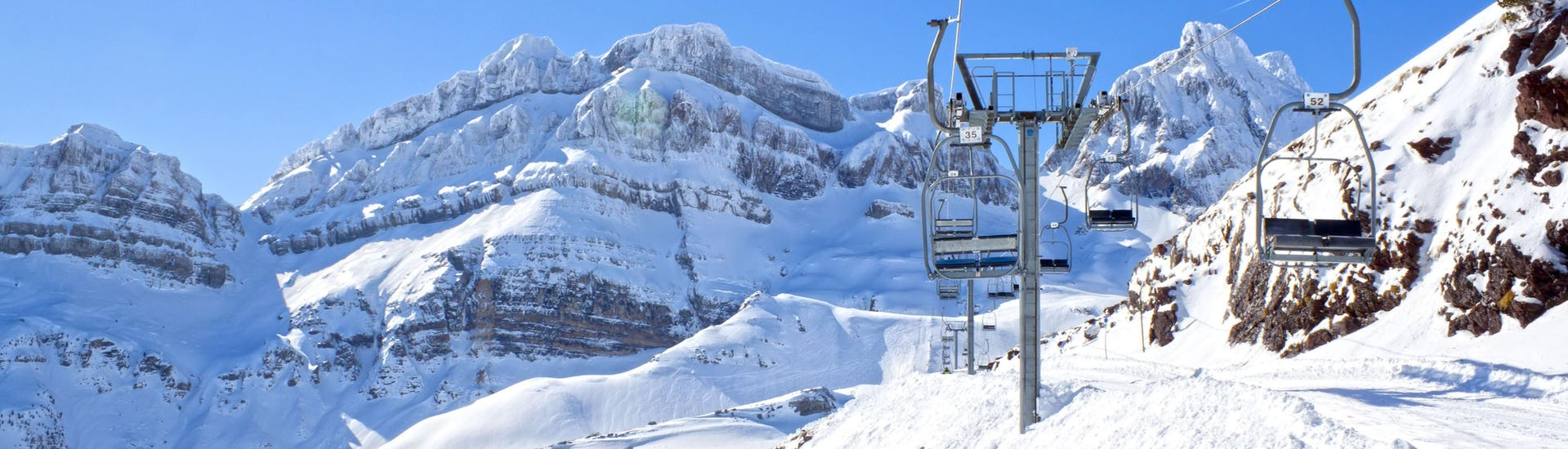 An image of a ski lift in the Spanish ski resort of Candanchú, where local ski schools offer all sorts of ski lessons to those wish to learn to ski.