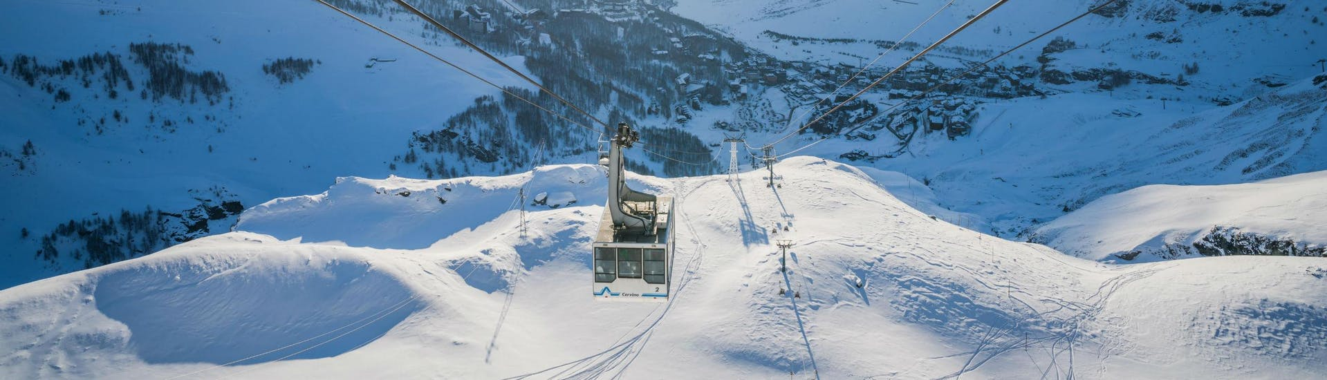 An image of a cable car ascending the mountain in the italian ski resort of Cervinia, where visitors can learn to ski during their ski lessons provided by local ski schools.