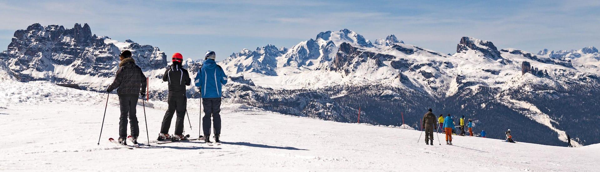 Vue panoramique sur les Dolomites avec des skieurs participants à des cours de ski des écoles de ski du domaine skiable Cortina d'Ampezzo.