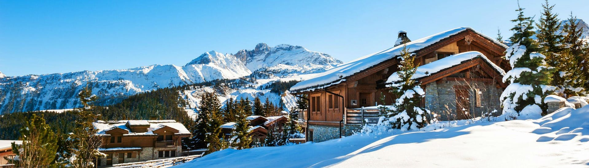 An image of a couple of snow-covered mountain huts in the popular French ski resort of Courchevel, where visitors can learn to ski in one of the many ski lessons organised by the local ski schools.