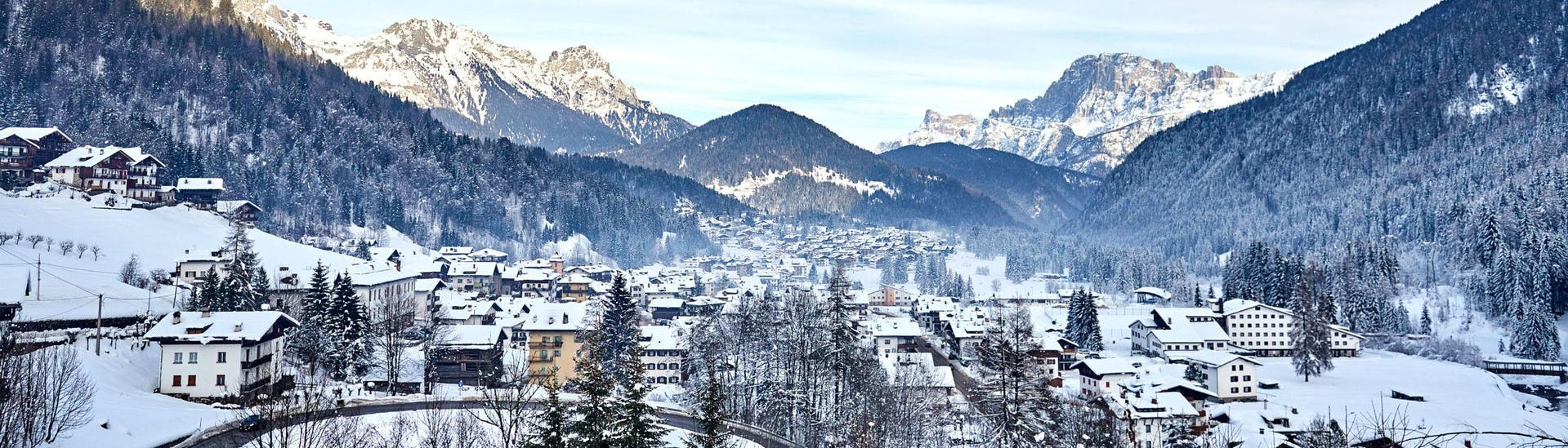 An image of Falcade, a picturesque Italian village nestled between the mountains, where aspiring skiers can book ski lessons with one of the local ski schools.