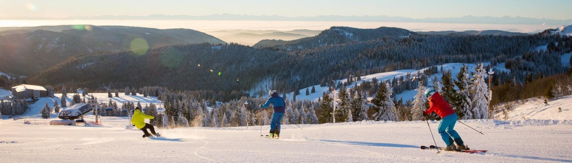 Twee skiërs en een snowboarder genieten van de zonnige witte pistes in Feldberg.