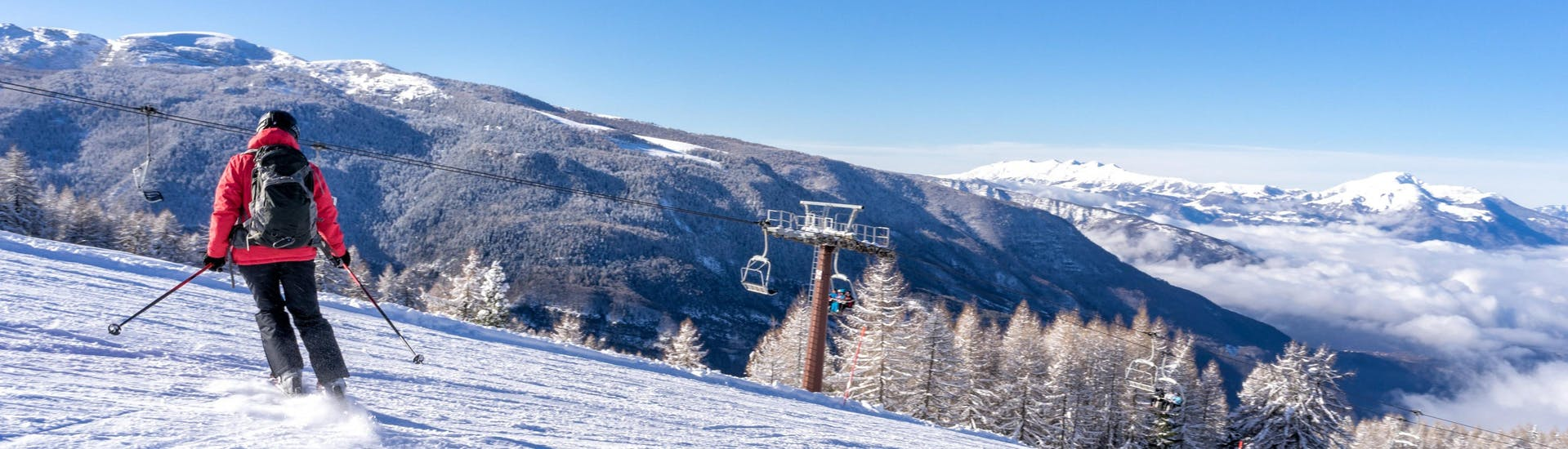 A woman is skiing with a ski school on a sunny day in Folgaria.