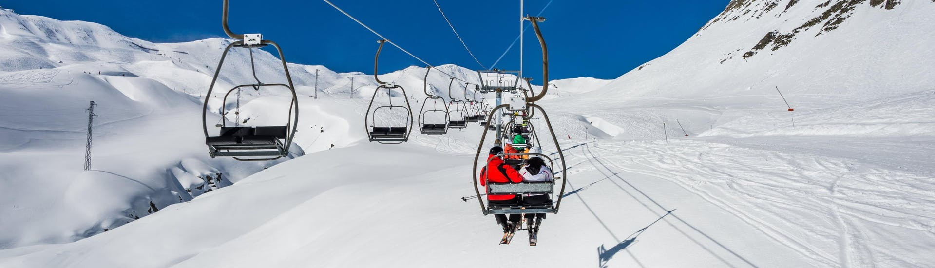 An image of a ski lift carrying skiers to the top of the ski slope in the Spanish ski resort of Formigal, where visitors who want to learn to ski can book ski lessons with local ski schools.