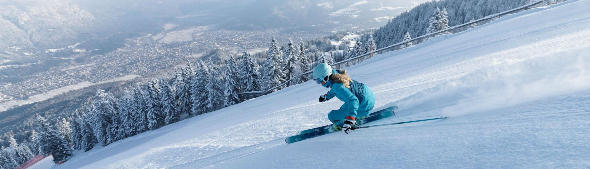 A female skier is speeding down a perfectly prepared slope overlooking the ski resort of Garmisch-Classic, where local ski schools offer a broad selection of ski lessons. (c)Bayerische Zugspitzbahn Bergbahn AGfendstudios.com