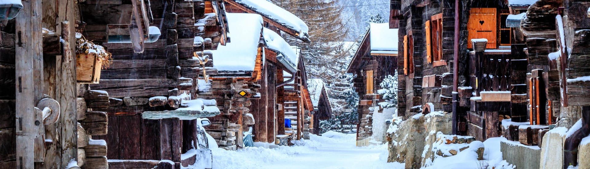 An image of the wooden chalets in the small Swiss ski resort of Grimnetz-Zinal, a popular destination for skiers who want to book ski lessons with one of the local ski schools.