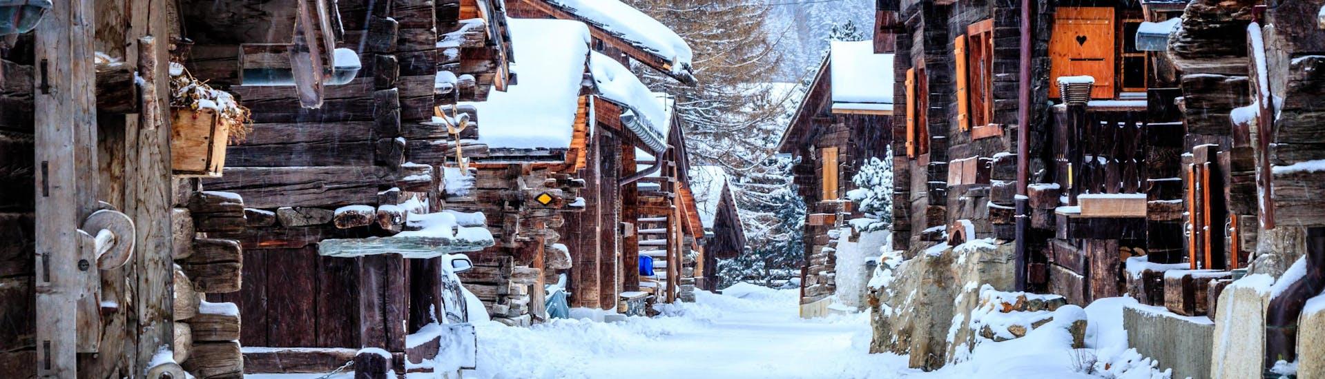 Une image des chalets en bois dans la petite station de ski suisse de Grimnetz-Zinal, une destination populaire pour les skieurs qui veulent réserver un cours de ski avec une des écoles de ski locales.