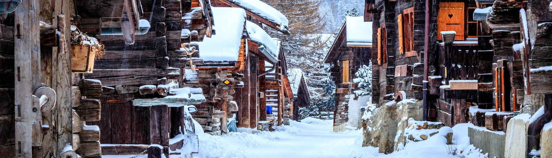 An image of the wooden chalets in the small Swiss village of Grimnetz, a popular destination for skiers who want to book ski lessons with one of the local ski schools.