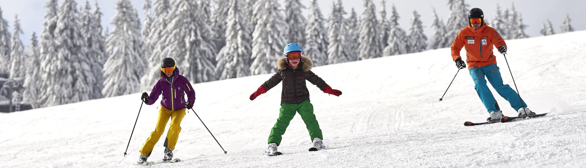 A family of two adults and one child is jointly skiing down a ski slope on Großer Arber, a popular German ski resort in which you can book ski lessons with one of the local ski schools.