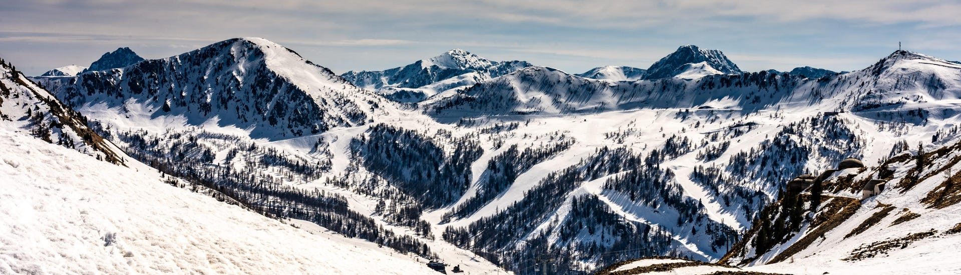 A panoramic view of the mountain peaks in the French ski resort of Isola 2000, where local ski schools offer a variety of ski lessons for people who want to learn to ski.