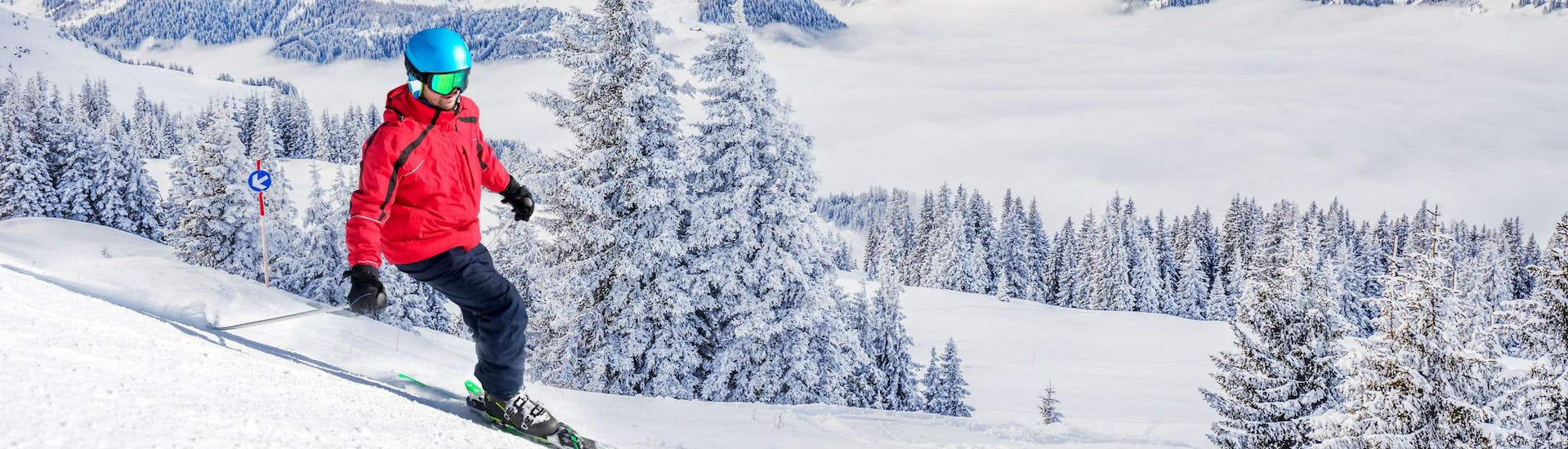 A skier is skiing down a ski slope with fresh powder snow and a stunning view of the surrounding Alps in the Kitzbühel area, where local ski schools offer a variety of ski lessons for anyone who wants to learn to ski.