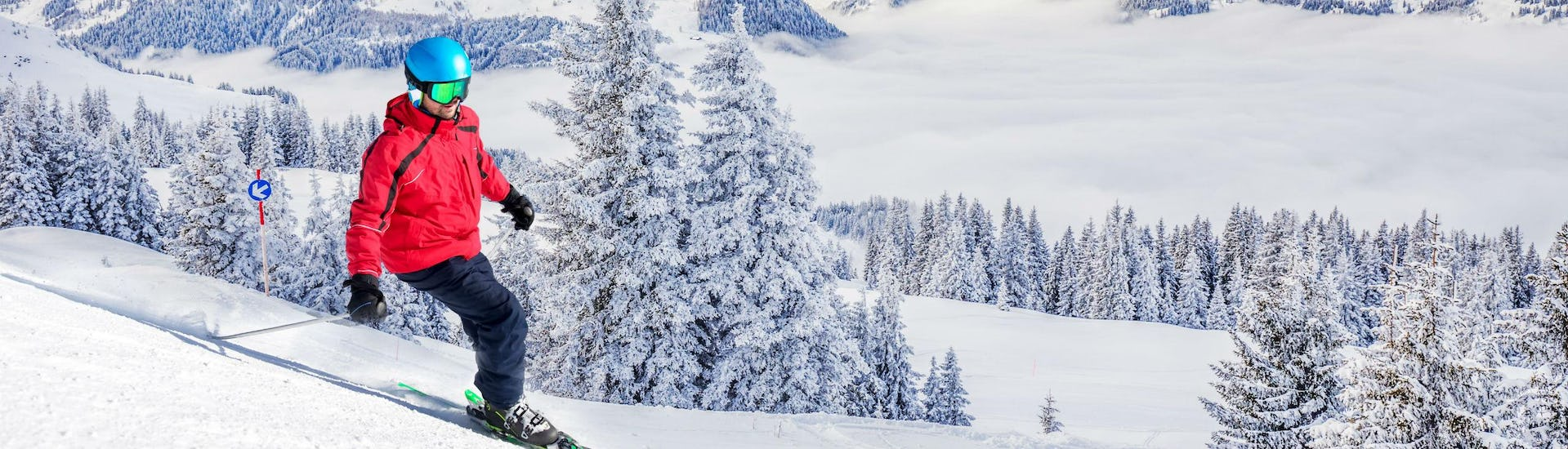 A skier is skiing down a ski slope with fresh powder snow and a stunning view of the surrounding Alps in the ski resort of Kitzbühel, where local ski schools offer a variety of ski lessons for anyone who wants to learn to ski.