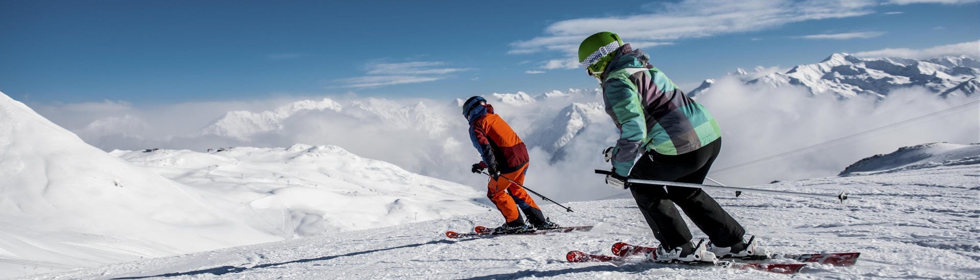 Two skiers are skiing down a freshly prepared slope in the Swiss ski resort of Klosters, a popular place to book ski lessons with one of the local ski schools.