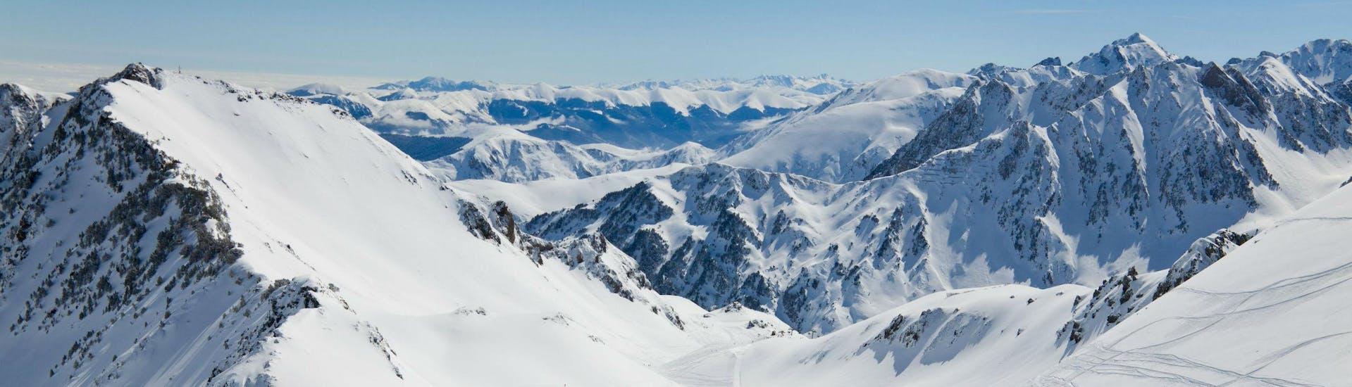Un snowboardeur admire la vue magnifique sur les Pyrénées enneigées depuis l'une des pistes de La Mongie - Village, où les écoles de ski locales proposent un vaste choix de cours de ski.