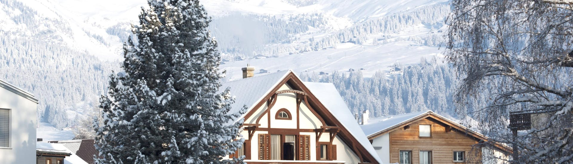An image of some of the snow-covered chalets in the Swiss ski resort of  Laax-Flims-Falera, where visitors can books ski lessons with one of the local ski schools.