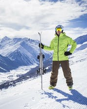 A skier is posing on one of the ski slopes in Livigno, overlooking the snow-covered ski resort from the top of the mountain.