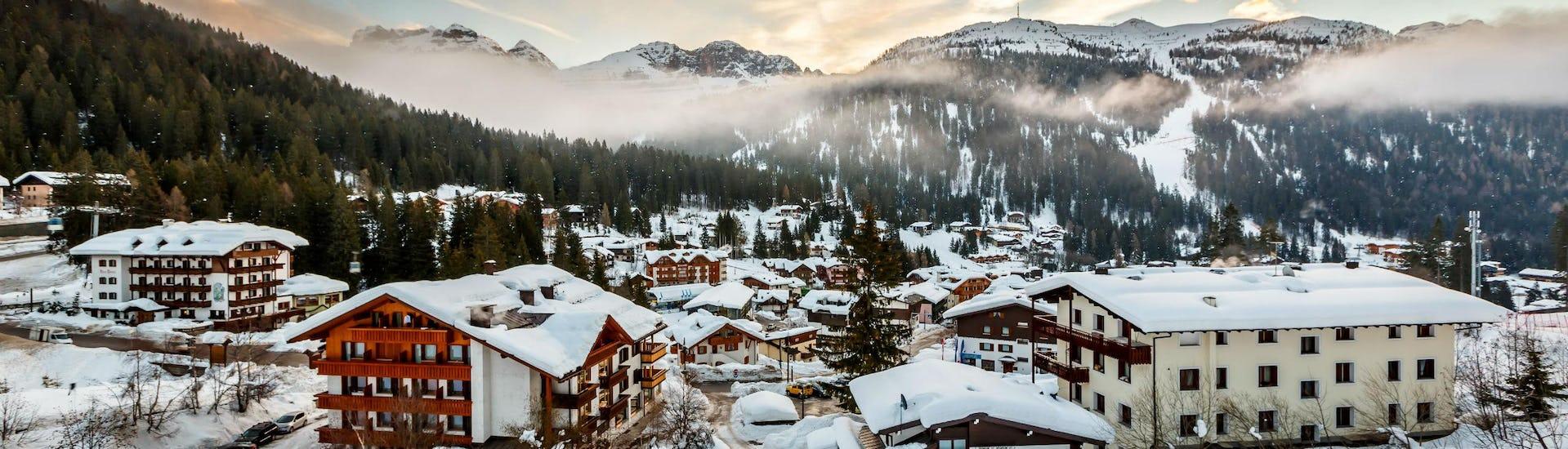 Immagine del sole che tramonta dietro le montagne nel comprensorio sciistico italiano di Madonna di Campiglio, dove i visitatori possono imparare a sciare durante le lezioni di sci impartite dalle scuole sci locali.