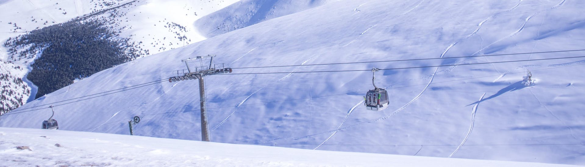 An image of a gondola carrying skiers up to the top of the mountain in the Catalonian ski resort of Masella, where visitors can book ski lessons with one of the local ski schools.