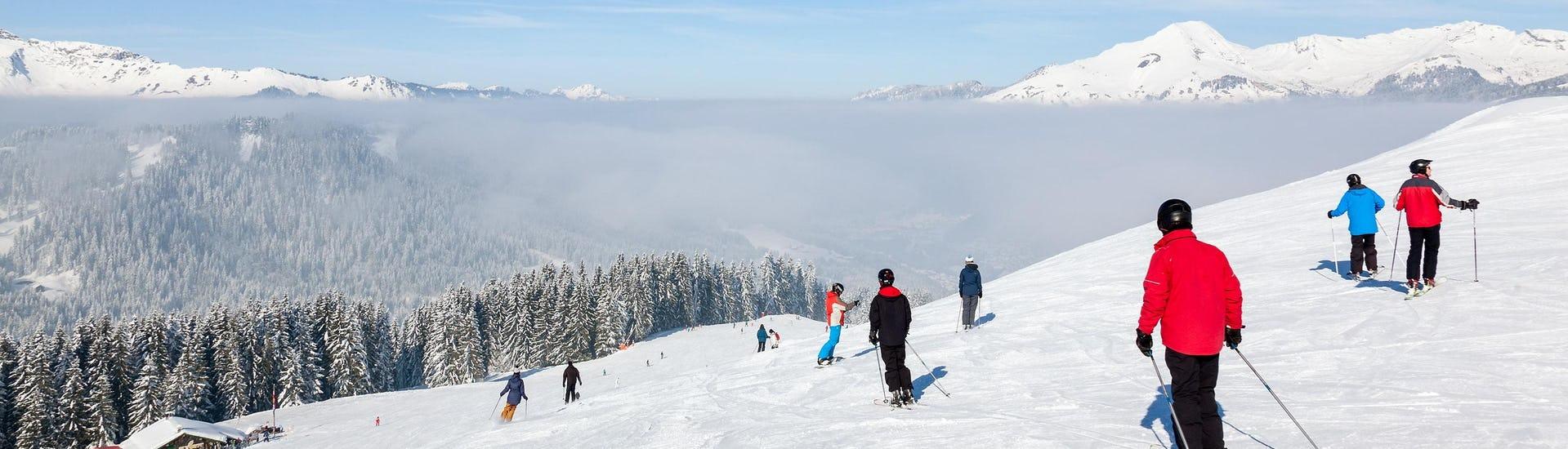 A number of skiers is skiing down a ski slope in the ski resort of Morzine, with a beautiful view of the surrounding mountainscape that is visible to all who book ski lessons with the local ski schools.