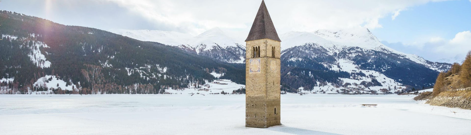An image the sunken church in Lake Reschen close to the Austrian ski resort of Nauders, where aspiring skiers can book ski lessons with one of the local ski schools.
