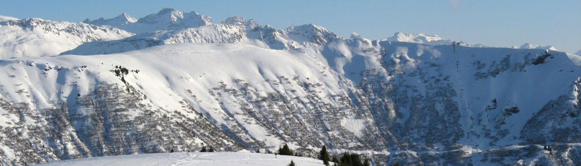 Une vue panoramique des pistes de ski de Notre Dame de Bellecombe, une station de ski française nichée entre les majestueux sommets du département de la Savoie, où les écoles de ski locales offrent un large choix de cours de ski.