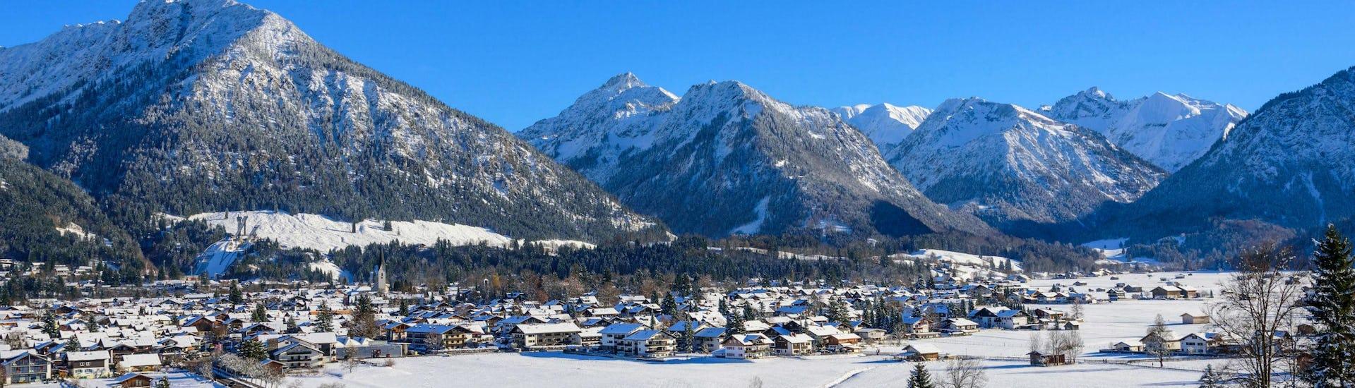 Een blik op het gezellige dorp Oberstdorf en de omringende bergen waar jong en oud van skilessen kan genieten.