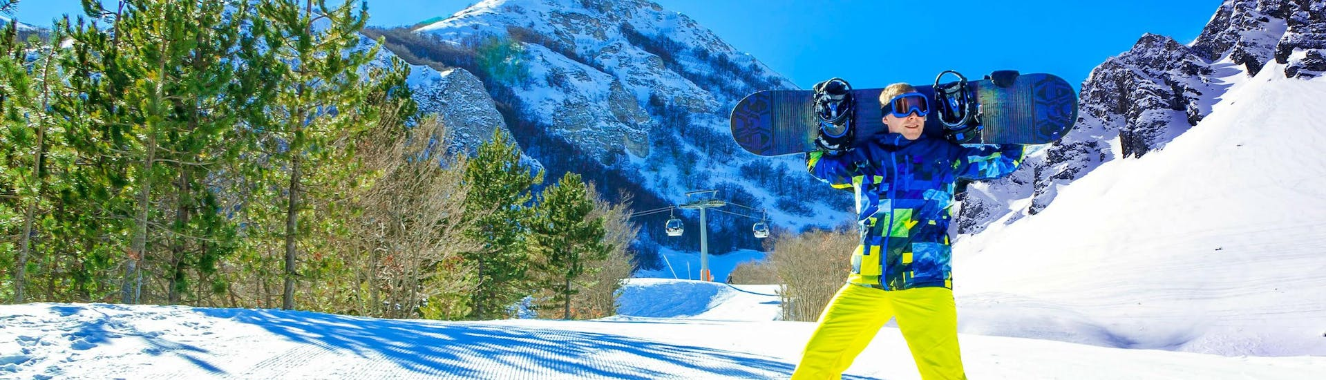 A snowboarder is posing for the camera on a sunny ski slope in the Italian ski resort of Ovindoli, where visitors can choose from a wide range of ski lessons offered by the local ski schools.