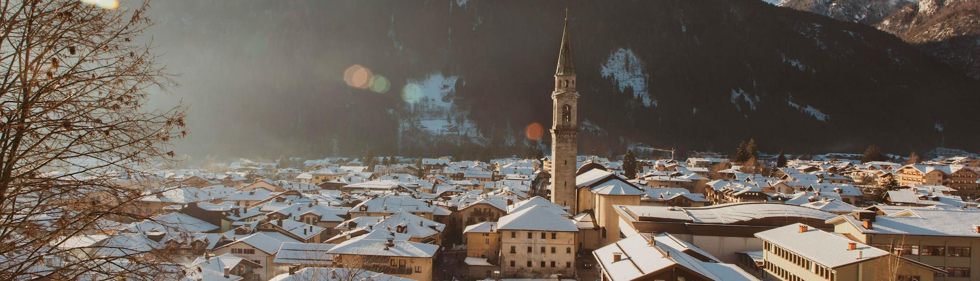 An image of the snow-capped roofs of the Italian village of Pinzolo, a popular destination for people to book ski lessons with one of the local ski schools.