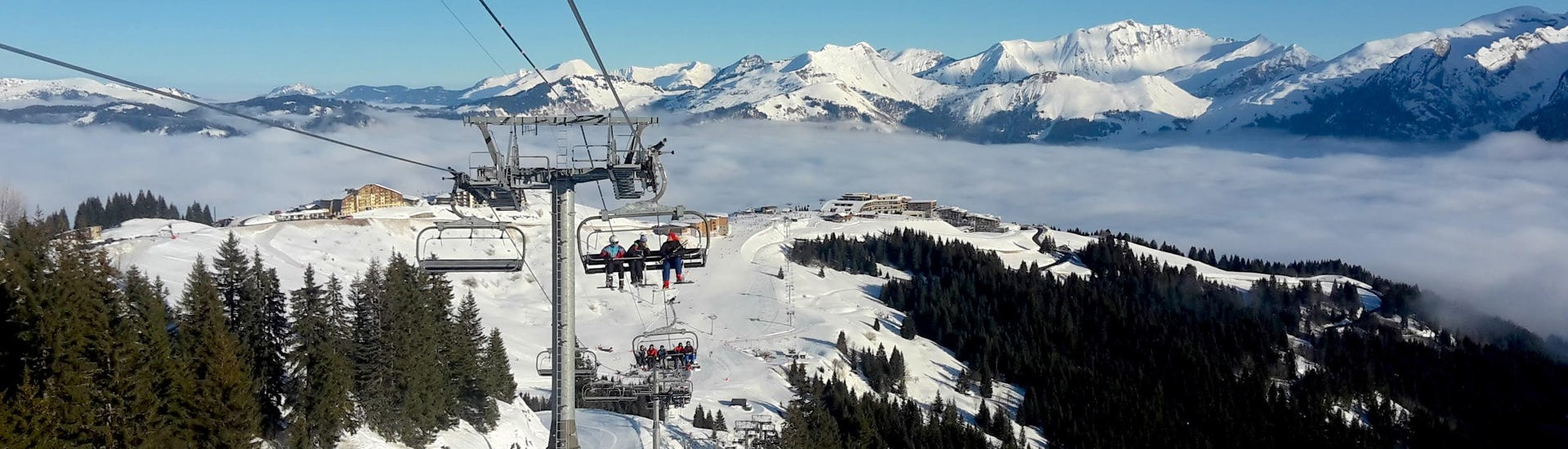 A chair lift in Samoens is carrying a group of skiers and their ski instructor from one of the local ski schools up to the top of the mountain where they will get started with their ski lessons.