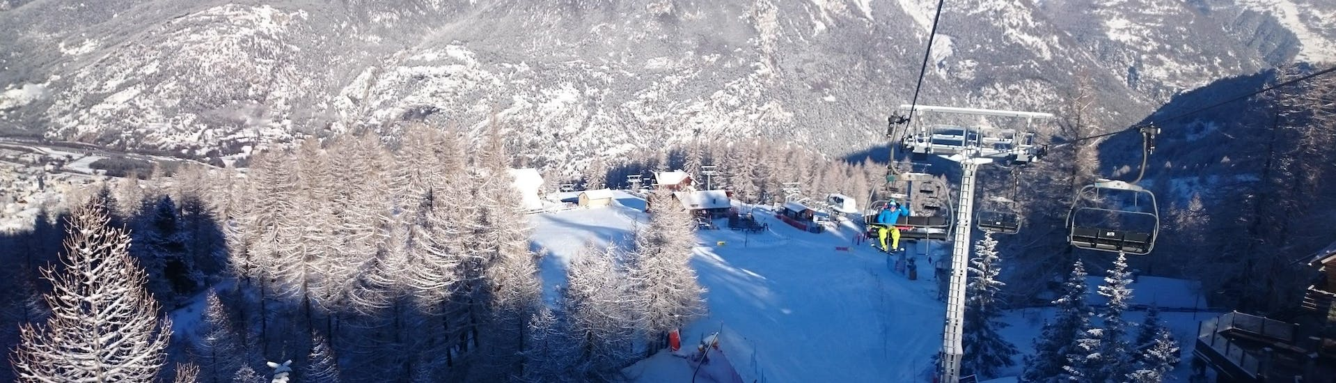 An image of a chair lift in the Italian ski resort of Sauze d'Oulx, where local ski schools take people for their ski lessons.