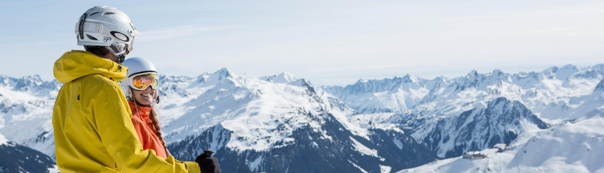 A man and a woman are looking out over the beautiful panorama of the Montafon mountain range, as they partake in their ski lessons with one of the local ski schools in Schruns.