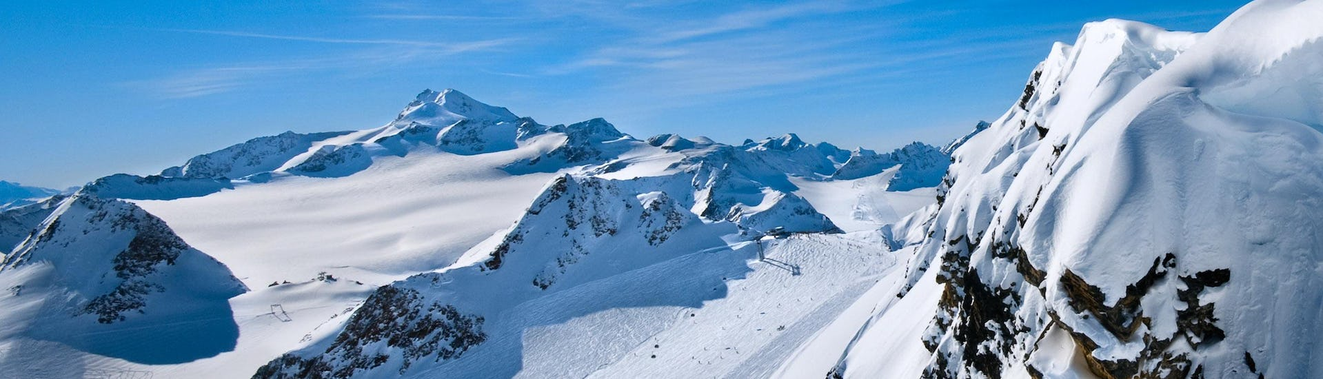 A view of a snowy mountain top in the ski resort of Arc 1800, where ski schools gather to start their ski lessons.