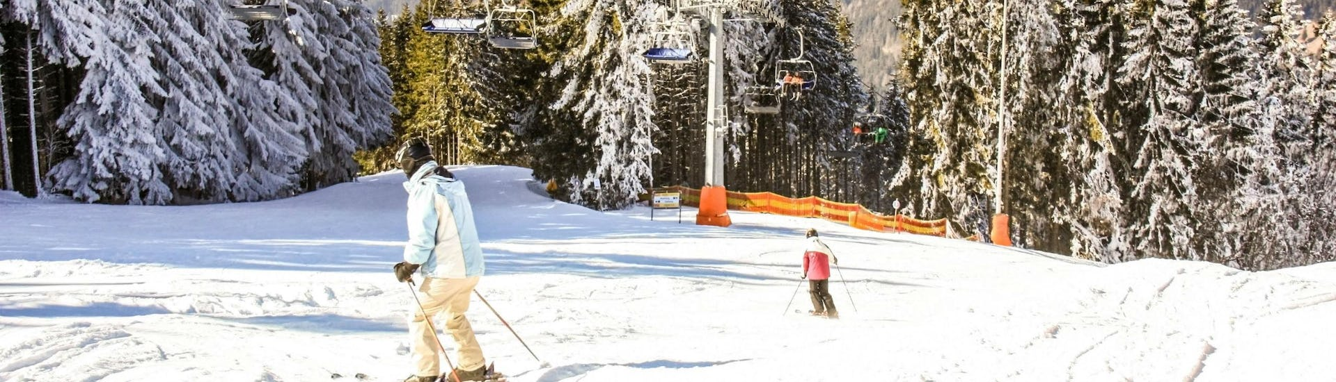 Two skiers are skiing down one of the ski slopes in the ski resort of Zauberberg-Hirschenkogel, where visitors can book ski lessons with the local ski schools.