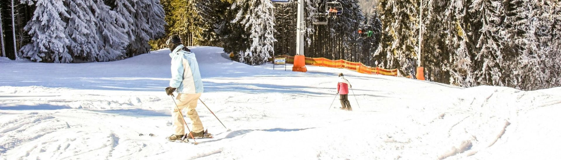 Two skiers are skiing down one of the ski slopes in the ski resort of Semmering, where visitors can book ski lessons with the local ski schools.