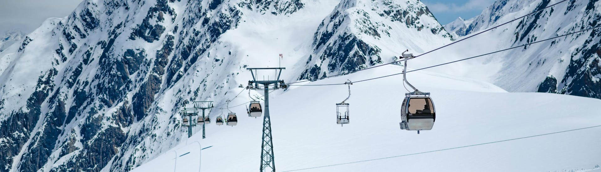 An image of a gondola carrying skiers to the top of the Stubai Glacier, where local ski schools carry out their ski lessons.