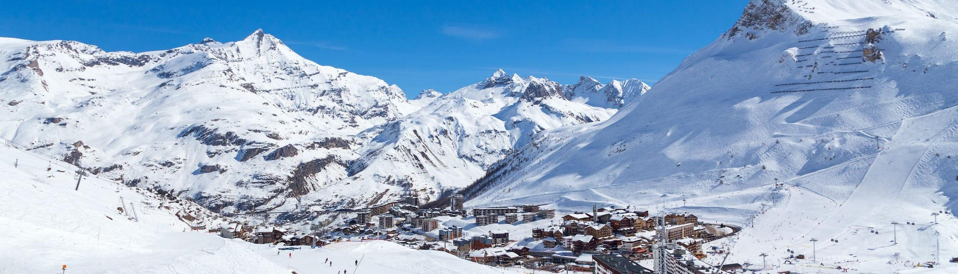 A view of the French ski resort of Tignes under the clear blue sky with its many pistes used by the local ski schools to carry out their ski lessons.