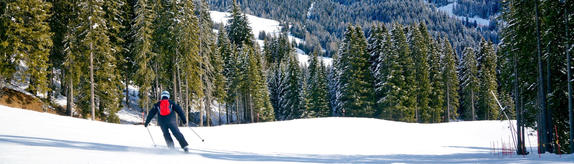 A skier can be seen skiing down a deserted ski slope in Val di Fassa, a popular place to book ski lessons with one of the local ski schools.