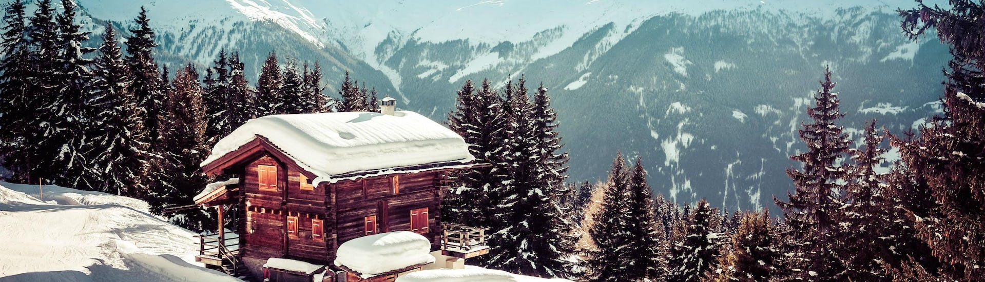 An image of a lone snowboarder boarding past a small mountain hut in the swiss ski resort of Verbier, where where visitors can learn to ski during their ski lessons provided by local ski schools.