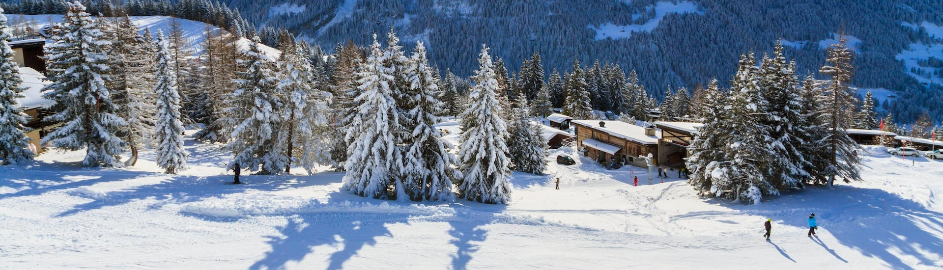 A panoramic view of the ski slopes and the surrounding mountains of Villars, a popular Swiss ski resort where visitors can book ski lessons with one of the local ski schools.