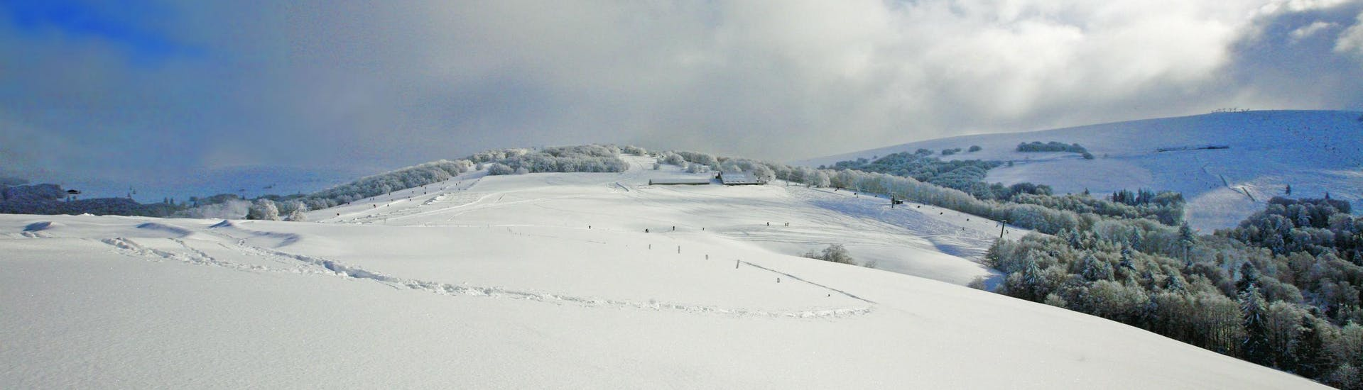 An image of the snow-covered hills in the French department of Vosges, where local ski schools offer a selection of ski lessons.