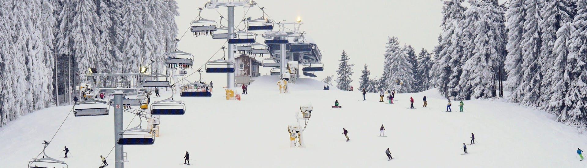 Een wit besneeuwd landschap met skiërs op een helling in Winterberg.
