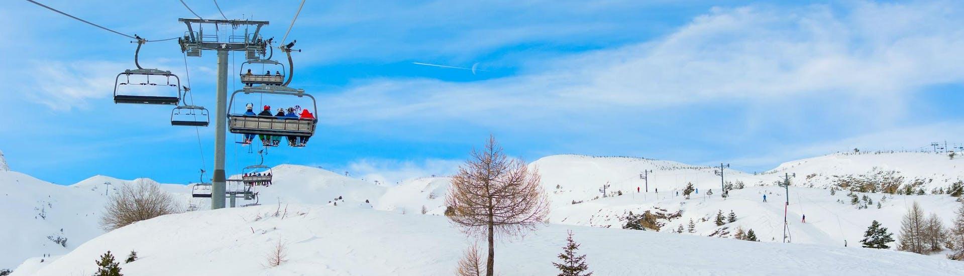 Un télésiège transporte des skieurs jusqu'au sommet de la montagne dans la station de ski française du Dévoluy, où les écoles de ski locales offrent une variété de cours de ski.