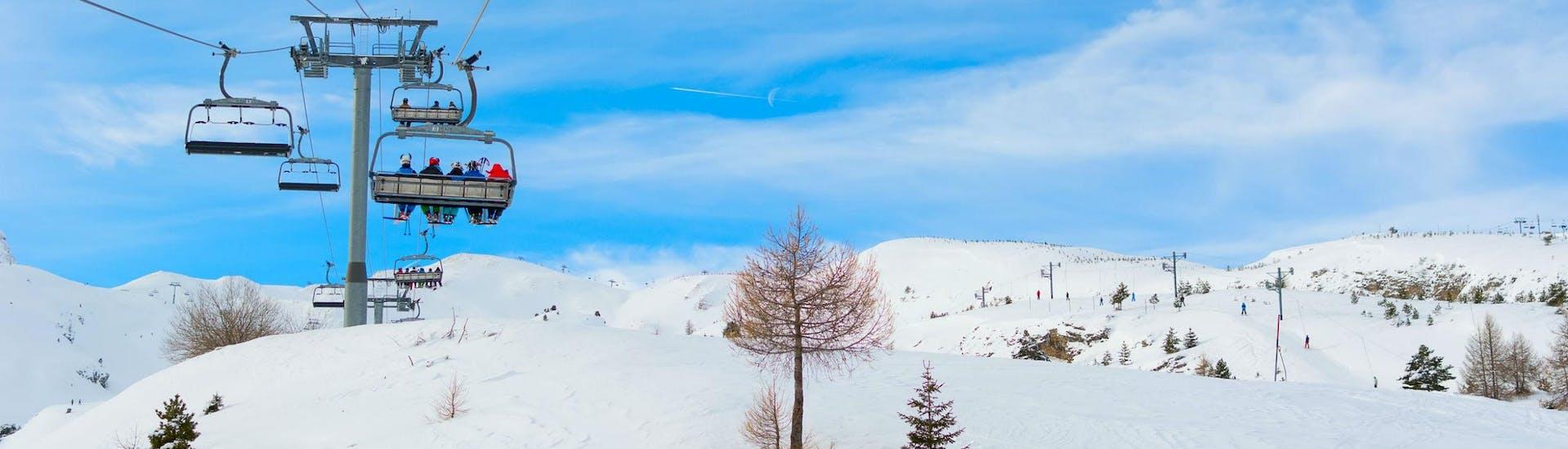 Un télésiège transporte des skieurs jusqu'au sommet de la montagne dans la station de ski française de SuperDévoluy, où les écoles de ski locales offrent une variété de cours de ski.