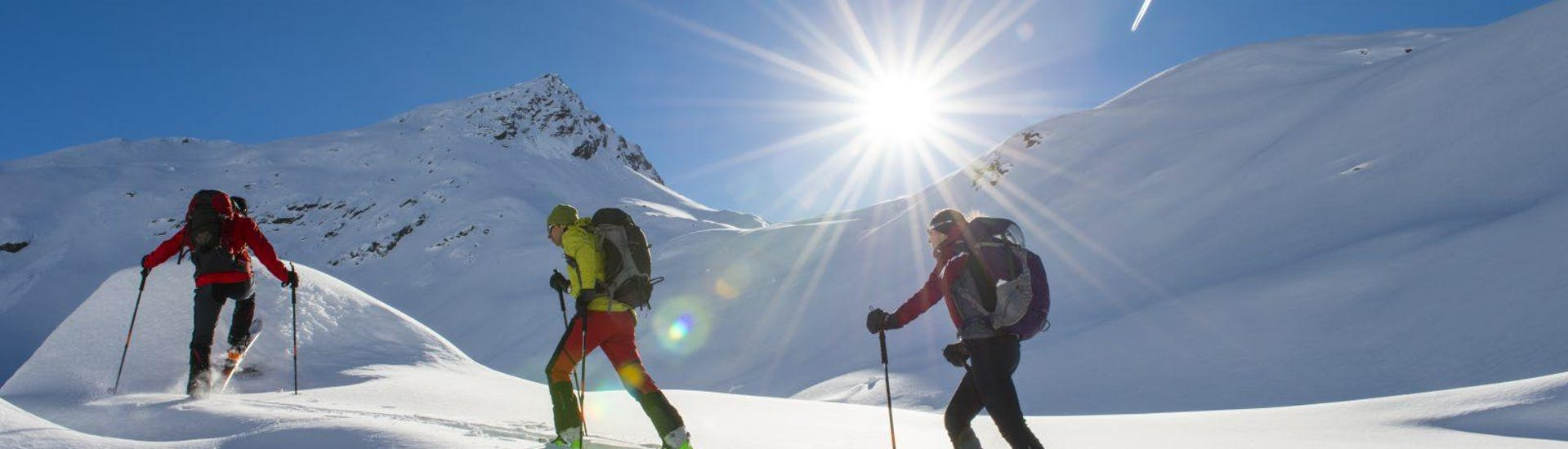 Two friends are walking through the snow-covered mountain landscape together with their Ski Touring Guide for All Levels from Bergführer Salzburg.