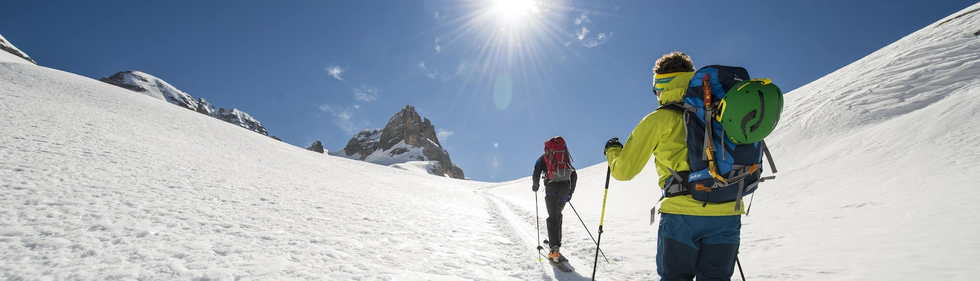 A ski touring guide is guiding another skier to the mountain summit while on a ski tour in the ski resort of Claviere.