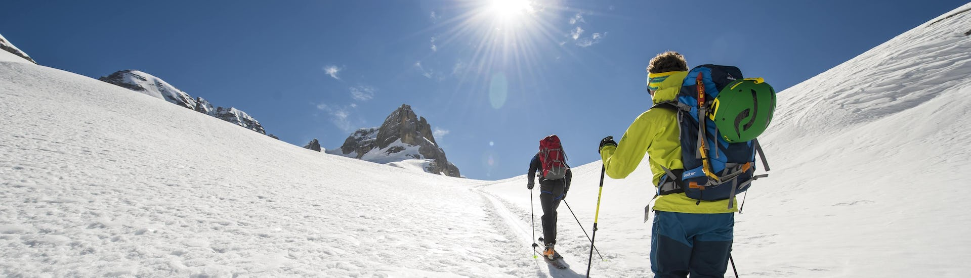 A ski touring guide is guiding another skier to the mountain summit while on a ski tour in the ski resort of Méribel.