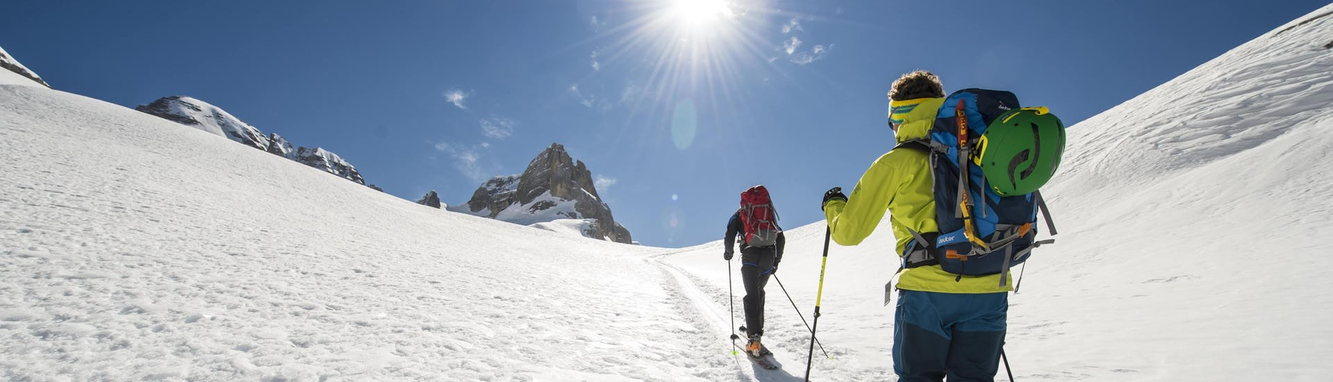 A ski touring guide is guiding another skier to the mountain summit while on a ski tour in the ski resort of Saas-Fee.