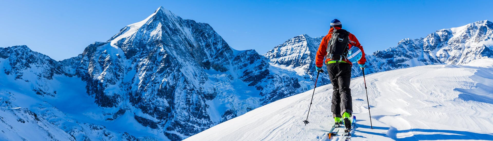 A man is exploring the snowy mountain landscape while ski touring in Czech Republic.